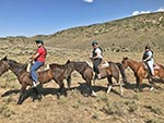 Three horseback riders smile as they ride past the camera.