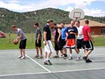 A group of young men line up for free throw practice at the Sports Court.