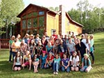 A girls' camp group poses for a photo outside our Red Creek Lodge.