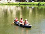 Three girls guide their canoe across the lake.