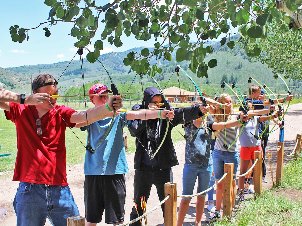 These boys all aim and prepare to fire off arrows at the same time at the Archery activity.