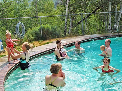 Parents and their babies spend time in the Red Creek Lodge's pool. Swim diapers required for all babies in the pool.