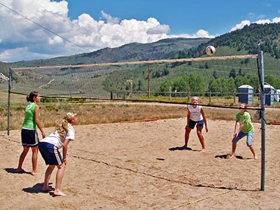 Two pairs of girls playing sand volleyball.