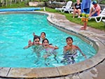 Four children playing in the pool, stop to wave at the camera.