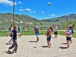 A group of youth keep their eyes on the ball in the sand volleyball court.