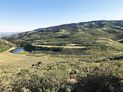 From high up on the mountainside one can view Reid Ranch's lake and plateau with facilities and activities ant-like in the distance.