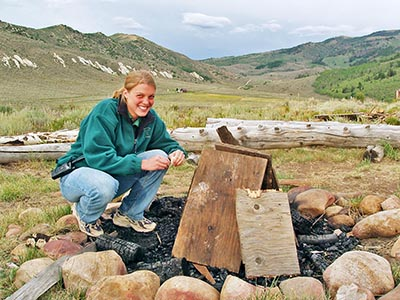A Reid Ranch employee is ready to light the campfire at the Bunkhouse Fire Pit.